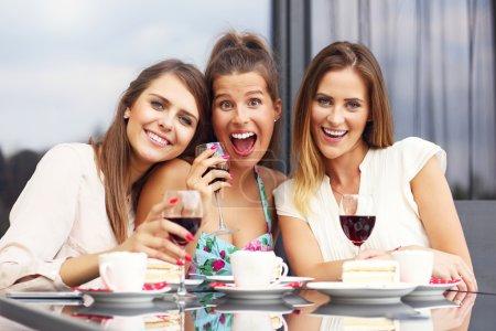 Photo pour Photo présentant un groupe d'amis bavarder dans un café - image libre de droit