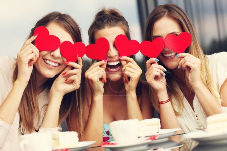 Photo for Picture presenting three girlfriends holding hearts in cafe - Royalty Free Image
