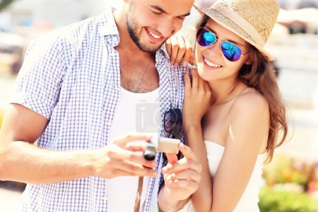 Joyful couple checking pictures on the camera
