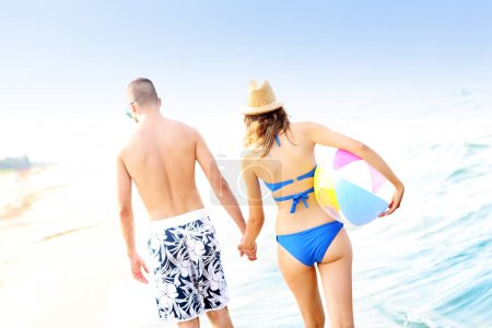 Foto de Una vista trasera de una joven pareja caminando por la playa - Imagen libre de derechos