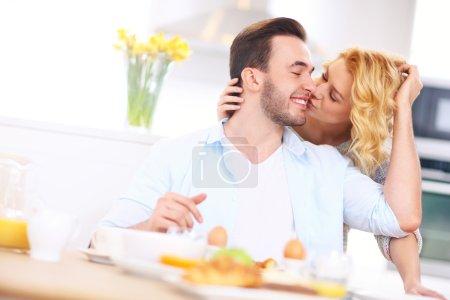 Photo pour Une photo d'une jeune femme heureuse donnant baiser de bon matin à son mari - image libre de droit
