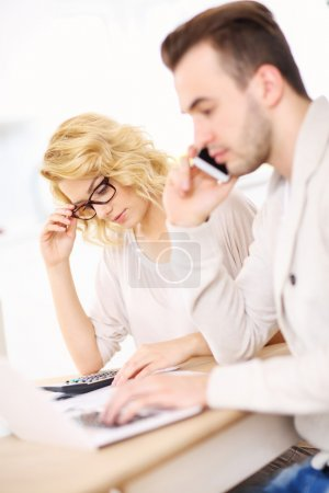 Worried couple with documents at home