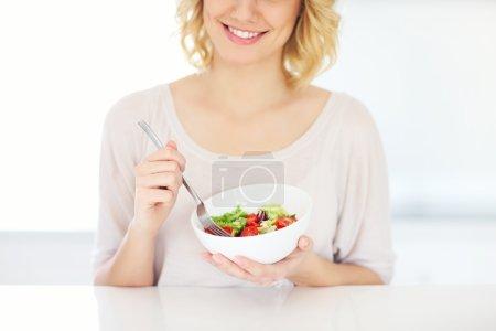 Photo pour Une photo d'une jeune femme mangeant de la salade dans la cuisine - image libre de droit