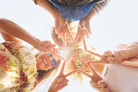 Photo for A picture of group of happy friends showing signs - Royalty Free Image