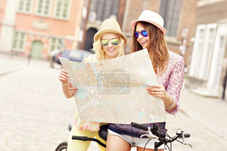 friends using map and bicycle