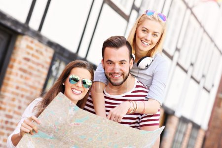 Happy friends sightseeing with map
