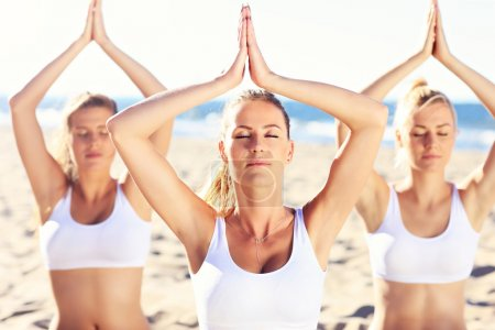 Group of women practicing yoga on the beach