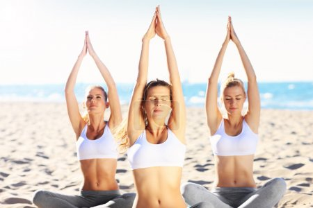 Photo for A picture of a group of women practicing yoga on the beach - Royalty Free Image