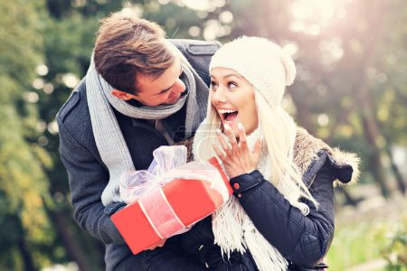 Photo for A picture of a young couple with a present in the park - Royalty Free Image