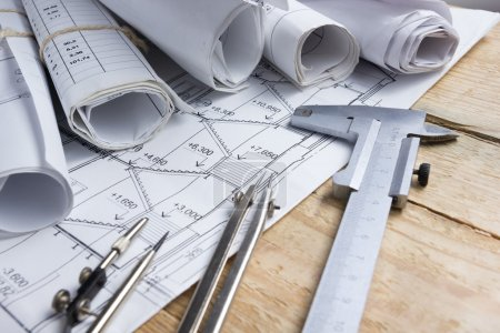 Architectural project, blueprints, blueprint rolls and divider compass, calipers on vintage wooden background. Construction concept. Engineering tools. Copy space