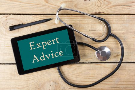 Expert Advice - Workplace of a doctor. Tablet, medical stethoscope, black pen on wooden desk background. Top view