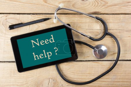 Need help ? - Workplace of a doctor. Tablet, medical stethoscope, black pen on wooden desk background. Top view