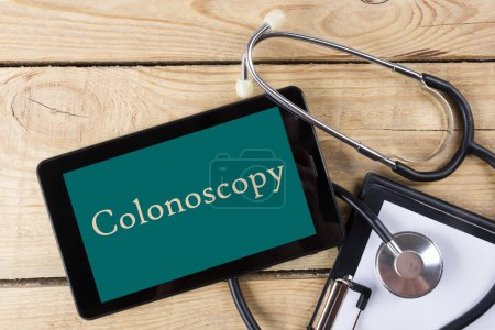 Colonoscopy - Workplace of a doctor. Tablet, stethoscope, clipboard on wooden desk background. Top view