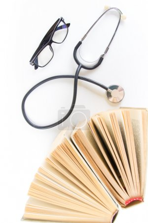 Open hardback books on the table, stethoscope and glasses. Top view. Medical professional education and information concept. Back to school, copy space.