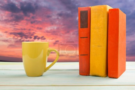 Stack of colorful books and cup on wooden table on natural blurred background. Back to school. Copy space