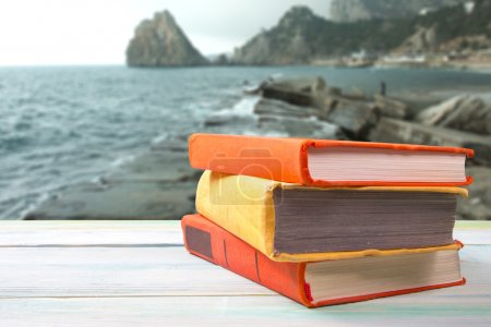 Stack of colorful books on wooden table on natural blurred background. Back to school. Copy space