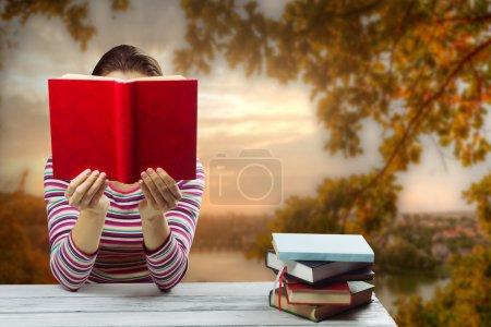 Photo pour Jeune femme lisant un livre et couvrant son visage, assis par table en bois avec pile de livres cartonnés colorés sur la nature floue paysage toile de fond - image libre de droit
