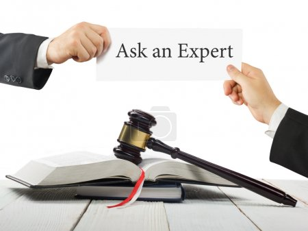 Law book and wooden judges gavel on table in a courtroom or law enforcement office. Lawyer Hands holding business card with text Ask an Expert