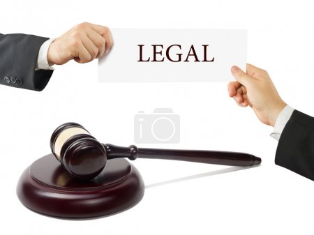 Wooden judges gavel on table in a courtroom or law enforcement office. Lawyer Hands holding business card with text Legal