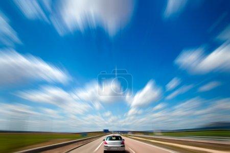Photo pour Road trip. Ciel bleu et voiture. Flou de mouvement et vitesse - image libre de droit