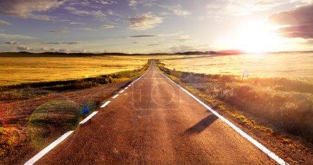Photo pour Aventures et voyages routiers.Coucher de soleil et concept de voyage.Route et champs - image libre de droit
