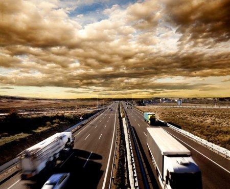 Foto de Embarque internacional, camiones y coches que conducen por la carretera. Logística y almacenamiento - Imagen libre de derechos
