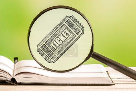 Photo pour Recherche de billets avec un dessin d'une icône de billet dans une loupe au crayon - image libre de droit
