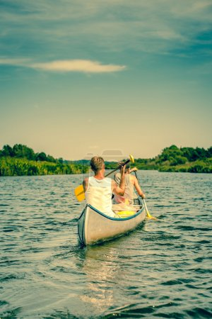 Photo for Two men rowing down a river stream in a canoe - Royalty Free Image