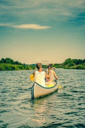 Two men rowing down a river