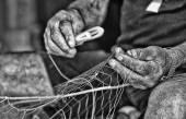 Old fisherman's village of Trani intent to mend fishing nets BW
