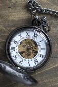Kapesní hodinky na rustikální dřevěné pozadí