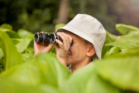 excited young camper hiding in grass looking through binoculars