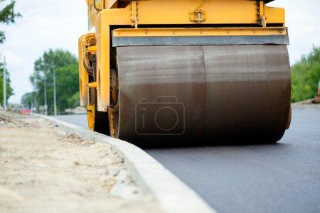 Orange road-roller on repairing of the road
