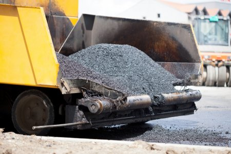 Tracked paver laying fresh asphalt pavement  during road constru