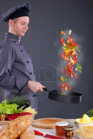 Photo for Professional chef throws food in the pan - Royalty Free Image