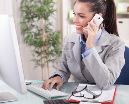 businesswoman talking on the phone in office and working on comp