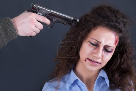 Terrorists holding a gun to a woman's head
