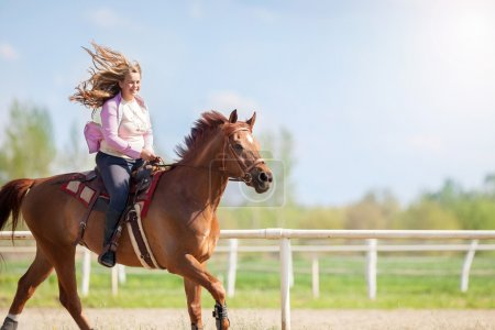 girl riding her brown horse in a training field
