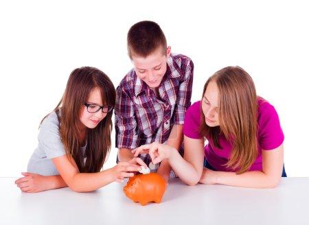 Photo pour Trois adolescents collectant l'argent ensemble pour leur future entreprise. Ils ont mis des pièces de monnaie dans la tirelire - image libre de droit