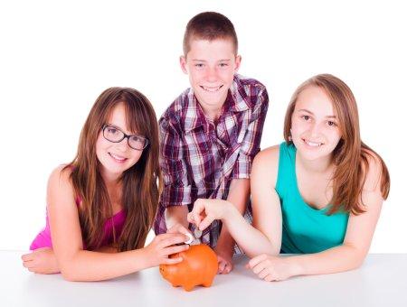 Photo pour Trois adolescents de mettre des pièces dans la tirelire, économiser de l'argent pour leur future entreprise - image libre de droit