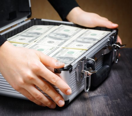 Business man opens an aluminum briefcase full of stacks of hundr