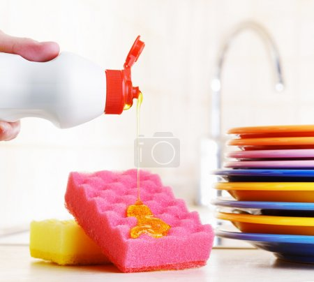 Photo for Several colorful plates, a kitchen sponges and a plastic bottle with natural dishwashing liquid soap in use for hand dishwashing. Eco-friendly, toxin-free, green cleaning product. Dishwashing concept. - Royalty Free Image