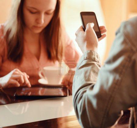 Photo pour Couple ignorant l'autre occupé avec leurs appareils mobiles dans le café. Petite amie buvant du café et regardant dans l'ordinateur tablette près de son petit ami en utilisant Smartphone . - image libre de droit