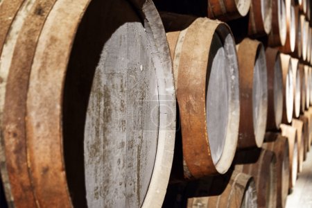 Closeup view of oak barrels stacked in the old cellar with aging