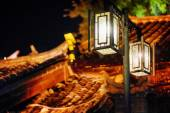 Noční pohled na pouliční lampy a tradiční čínština dlaždic střechy
