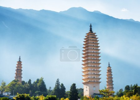 Photo for The Three Pagodas of Chongsheng Temple near Dali Old Town, Yunnan province, China. Scenic mountains are visible in background. Ancient pagodas are a popular tourist destination of Asia. - Royalty Free Image