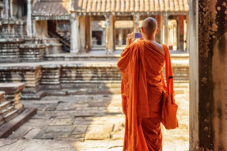 Buddhist monk with smartphone taking picture in Angkor Wat