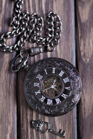 vintage pocket watch and key