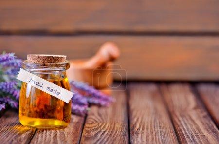 Photo pour Huile de lavande en bouteille en verre et fleurs de lavande fraîche sur table en bois - image libre de droit