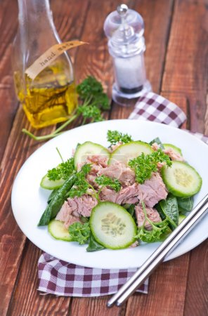 Salad with tuna on white plate